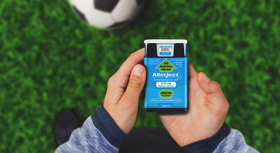 A child's hands holding a 0.15 mg dose ALLERJECT device against the backdrop of a soccer field.