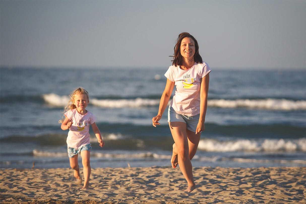 A woman and her daughter walking along a beach.
